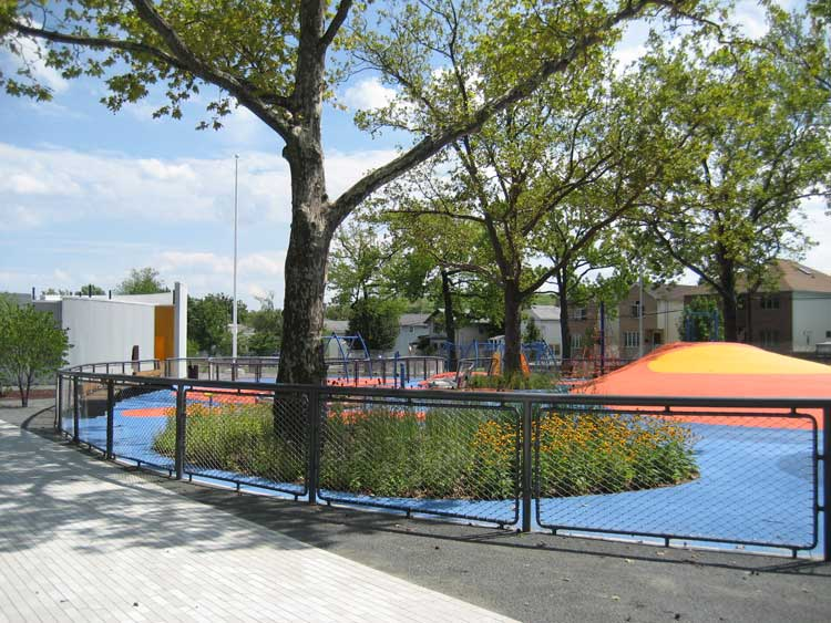 Schmul Park playground features colorful play structures and abundant greenery.