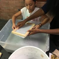 To make paper, participants dipped a mold into the native seed mix pulp.