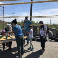 Visitors make wind chimes out of recycled objects